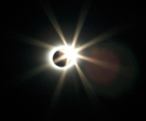 "The ""diamond ring"" as the sun peeks through a valley on the moon, while the corona is still visible."
