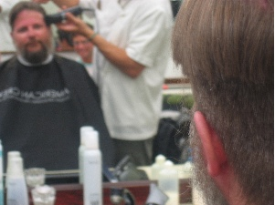 Getting hair and beard chopped off, amused onlookers